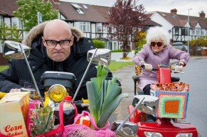 The Harry Hill Movie still- Harry Hill riding a mobility scooter being chased down the road by a lady in a mobility scooter