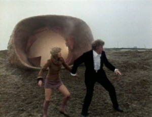 Doctor Who (Jon Pertwee) and Jo Grant (Katy Manning) holding hands running across a muddy floor.