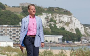 Great British Railway Journeys- presenter walking towards the camera with white cliffs behind