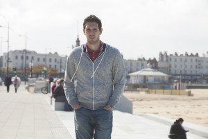 BLAKE HARRISON (Alfie) standing by the seaside with the beach and town behind him