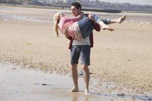 BLAKE HARRISON (Alfie) carrying JUSTINE CAIN (Carly) across the sandy beach
