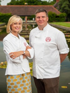 Britain's Best Bakery Judges Mich Turner and Peter Sidwell standing outside in front of a pond