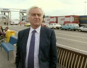Inspector Morse with his hands in his pockets looking at the camera with the port of dover queue behind him.