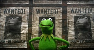 Kemit The Frog standing in front of a wanted poster with him on