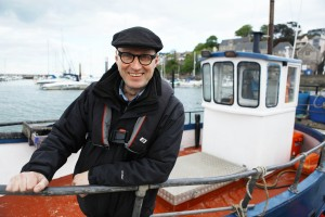 Ade Edmondson sitting on a boat