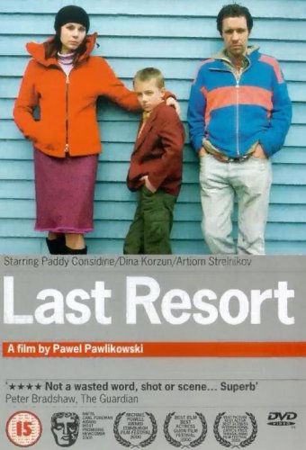 Last Resort dvd cover- a family standing against a blue cladded wall- the women is stood to the left with her arm around the boy in the middle, the man is to the right with his hands in his pockets. Last Resort is written in white