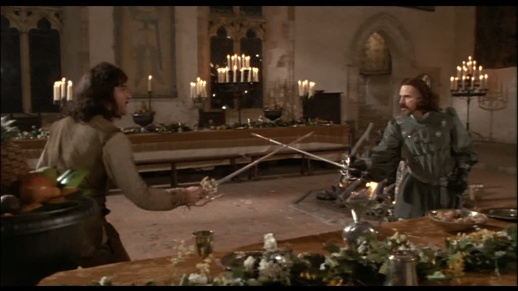 Inigo Montoya (Mandy Patinkin) and Count Rugen (Christopher Guest) duelling in a hall next to a long wooden table with food on it. Candles are in the background behind them.