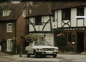 Dempsey and Makepeace driving through Chilham village in a white classic car.
