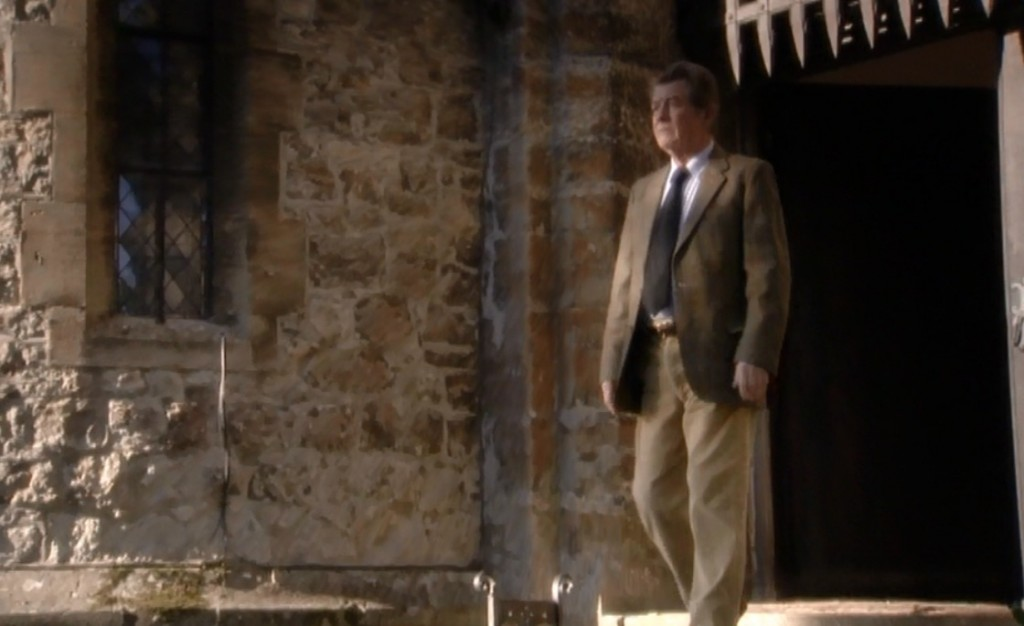 Alan Clark (John Hurt) is standing outside the doorway of Saltwood Castle on a sunny day. The castle grate can be seen above his head.