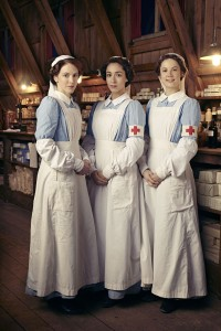 osalie Berwick (Marianne Oldham), Kitty Trevelyan (Oona Chaplin), Flora Marshall (Alice ST Clair) dressed as midwives standing in front of old fashioned shelves