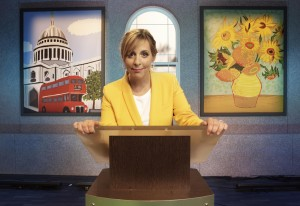 Mel Giedroyc wearing a yellow jacket standing in front of a podium in front of pictures