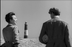 Joanna Godden (Googie Withers) and Martin (Derek Bond) on Dungeness beach. A black a white still with the lighthouse viable in the background as they walk on the stones. with their heads turned towards each other in mid conversation.