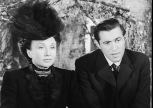 A black and white still of Joanna Godden (Googie Withers) and Arthur Alce (John McCallum). Behind them is an arch covered in flowers.