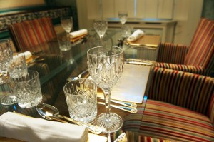 close up of a dinning table with striped chairs and wine glasses