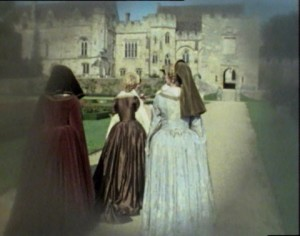 Elizabeth R at Penshurst Place walking towards the stone building, two other women in costume follow behind