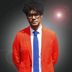Gadget Man Presenter Richard Ayoade in an orange suit and blue tie