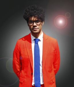 Gadget Man Presenter Richard Ayoade in an orange suit and blue tie