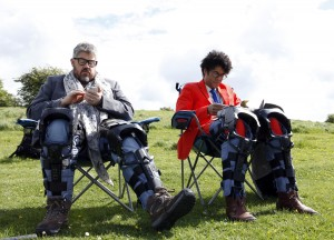 Richard Ayoade and Phill Jupitus sitting on chairs with gadgets on their legs