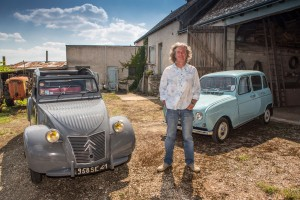 James May standing by a Renault 4 and Citroën 2CV in a farmyard in front of a barn in Blois, France