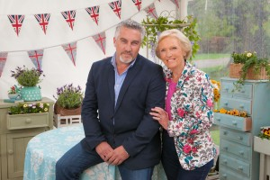 Paul Hollywood and Mary Berry in the Great British Bake Off tent perched on a table