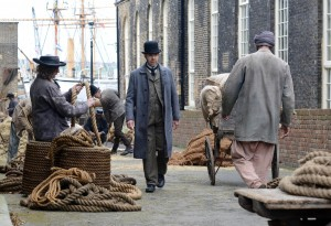 Paddy Considine walking along a street past a lady with baskets and rope. A ship can be seen in the background