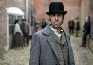 Mr Whicher standing staring at the camera on a cobbled street.