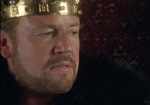 close up of Ray Winstone wearing a gold crown looking away from the camera