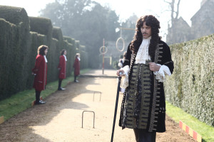 Jack Huston as Pepys in a garden with guards in a row against the hedges behind him
