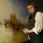 Mr Turner (Timothy Spall) standing in front of a painting
