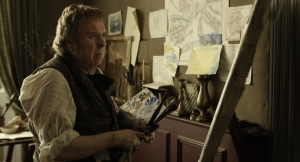 Mr Turner looking at a painting in his study. Paintings are also on the walls behind