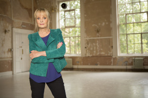 Twiggy standing with her arms crossed in a run down empty room