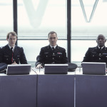 Jonny Sweet as Tom Oliver, James Nesbitt as Richard Miller and Paterson Joseph as Charles Inglis sitting at a desk in police uniforms