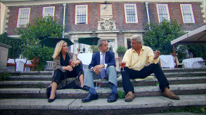 Steph and Dom sitting outside their home with Nigel Farage on some concrete steps