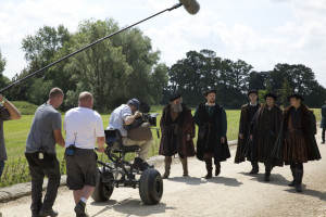 Mark Rylance as Thomas Cromwell and cast members behind the scenes on Wolf Hall being filmed by camera crew on a pathway