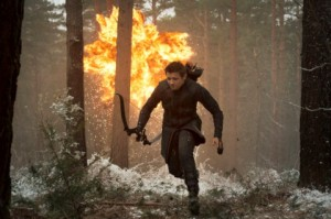 Hawkeye (Clint Barton) running through a snowy forest as there's an explosion in the background