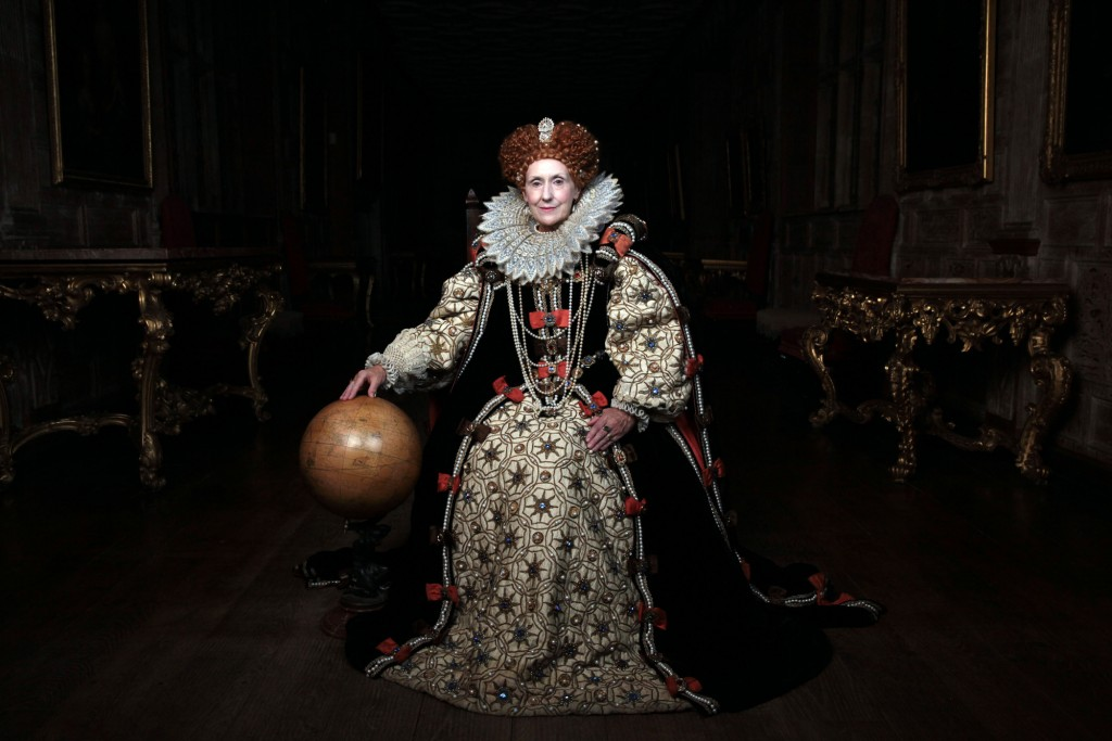 Anita Dobson as Queen Elizabeth I sitting in a large dark room with her hand on a globe
