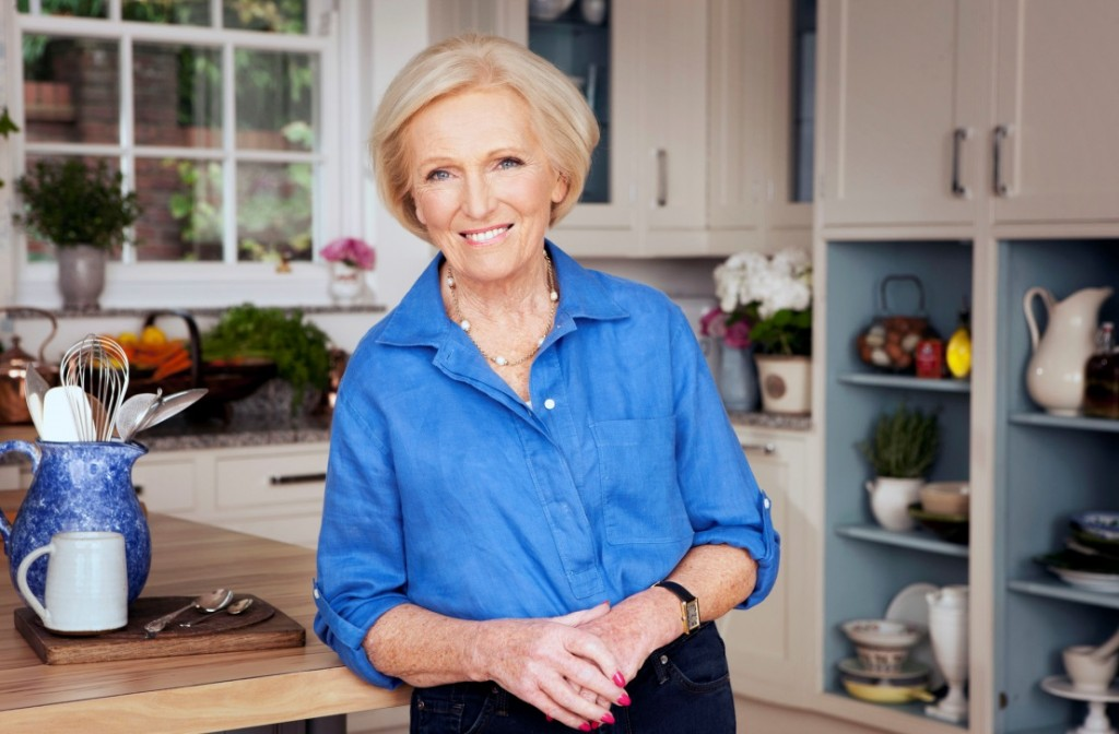 Mary Berry standing in front of a kitchen with her elbow leant against the counter top