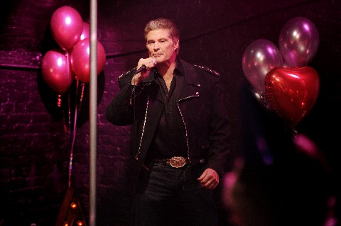 David Hasselhoff singing into a microphone in a club with pink balloons behind him