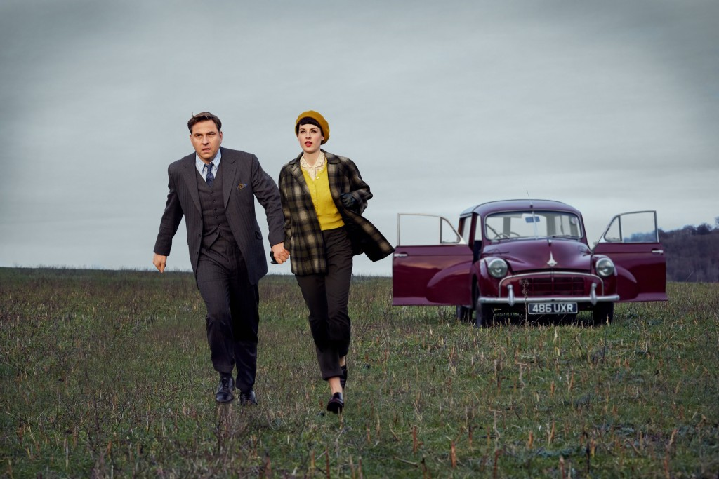 Tommy (David Walliams) pulling Tuppence (Jessica Raine) by the hand towards the camera in a field, a red car is behind with the doors open