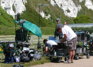 A small film crew of four with their filming equipment set up on some greenery in front of white cliffs.