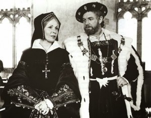 image of a man and women dressed in tudor costumes stood next to each other in front of a pillar