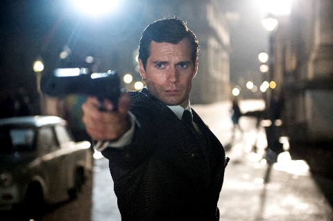 Henry Cavill pointing a gun to the camera in a street