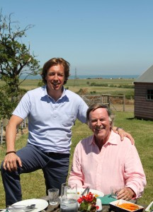 Terry Wogan sat outside on a table with food in front of him, Mason McQueen is stood up next to him with his arm on his shoulder. Countryside can be seen in the background.