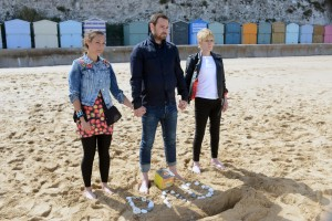 Tina Carter (LUISA BRADSHAW WHITE), Mick Carter (DANNY DYER) and Shirley Carter (LINDA HENRY) on a beach standing above pebbles spelling DAD