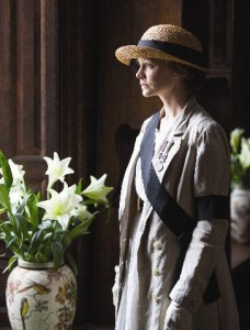 Carey Mulligan as Maud looking out of a window next to a vase of flowers