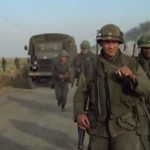 Soldiers walking in front of military truck.