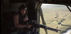 A man on a helicopter, firing a door gun in the film towards the river