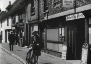 New Romney high street with a lady walking her bike on the pavement