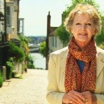 Penelope Keith standing in a picturesque British village