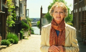 Penelope Keith standing in a picturesque British village with the sea visable behind